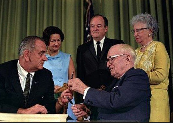 Harry and Bess Truman watch with Lady Bird Johnson as President Lyndon B. Johnson signs the Medicare Act, and made the elderly couple the first two recipients of the federal medical coverage. (LBJ Library)